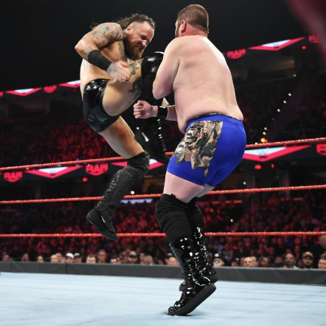 Aleister Black blasting local wrestler Jason Reynolds with a knee strike via WWE.com