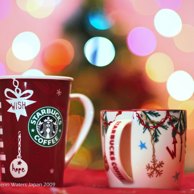 [Image Description: A red and a white coloured Christmas themed Starbucks cup kept in front of an unfocused Christmas tree.]
