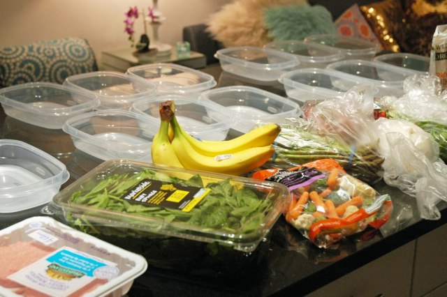 Multiple Tupperware containers on a table with various food items, setup for meal prep