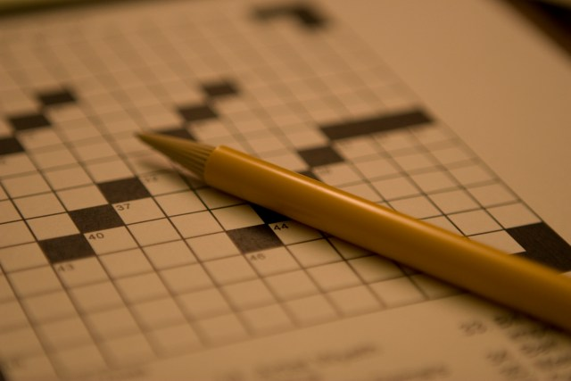 A yellow pen rests on an empty crossword puzzle.
