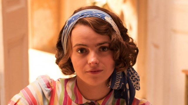 Image description: Margo is seen from the shoulders up. She is wearing a bright multicolored striped shirt and is wearing a blue patterned scarf in her hair.