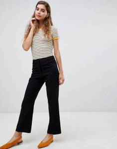 Image Description: A woman wearing black trousers, a striped t-shirt and coral shoes.