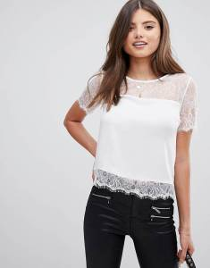 A woman wearing a white lace shirt and black jeans