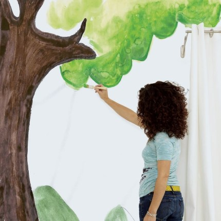 A woman with dark brown curly hair wearing a teal shirt and jeans paints a tree on a wall. Her back is to the viewer