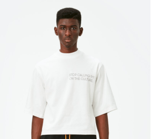 """[Image description: a Black man wearing a white shirt that reads """"stops calling 911 on the culture.""""]"""