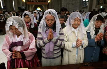 "South Korean Catholics pray for peace on the Korean Peninsula during an annual Easter service at Myeongdong Catholic Cathedral in Seoul, South Korea, Sunday, March 31, 2013. North Korea warned South Korea on Saturday that the Korean Peninsula had entered ""a state of war"" and threatened to shut down a border factory complex that's the last major symbol of inter-Korean cooperation.(AP Photo/Ahn Young-joon)"