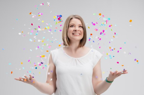A woman wearing a white top is throwing colourful confetti in the air. She is smiling.