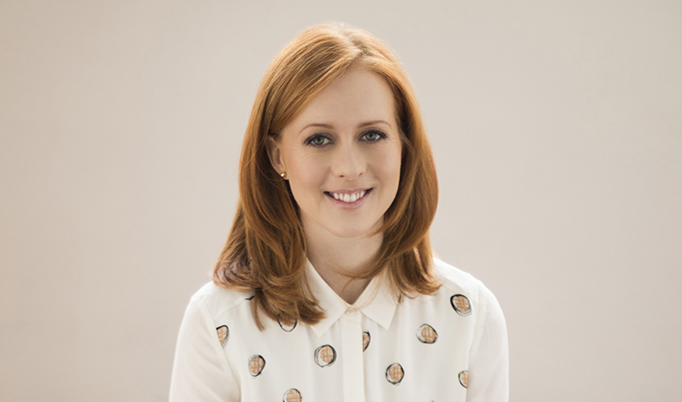 Portrait of Erin Rhodes. A woman with red hair wearing a white shirt smiling at the camera