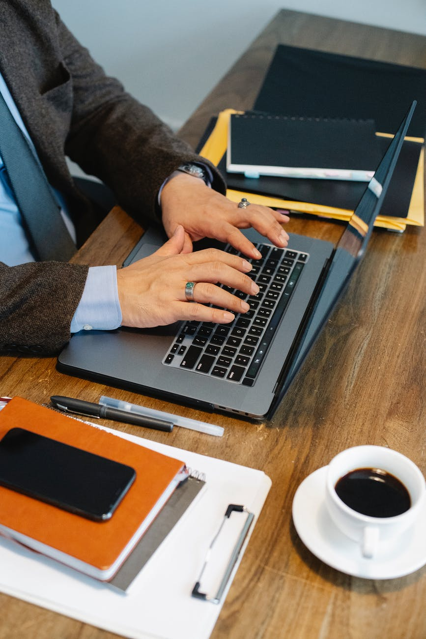 crop faceless businessman typing on laptop in office