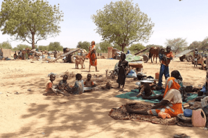 Refugees fleeing recent violence in Sudan's Darfur region sit in shade near the town of Adre, Chad. © UNHCR