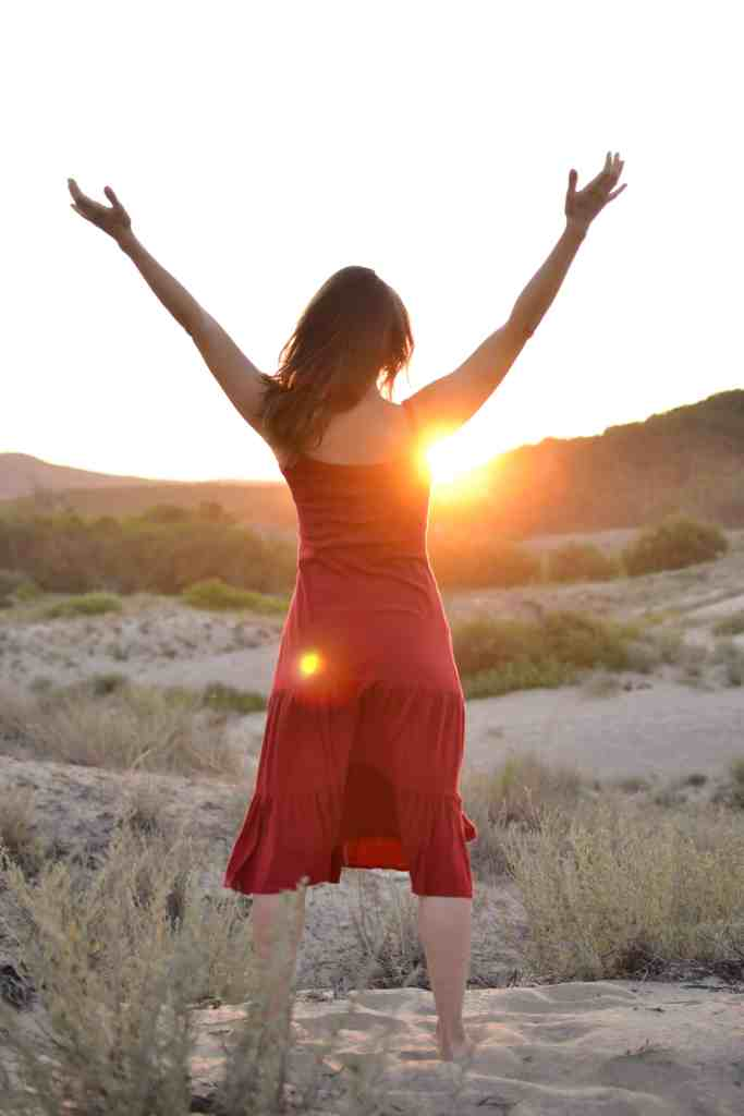 Woman in a red dress greeting the sun