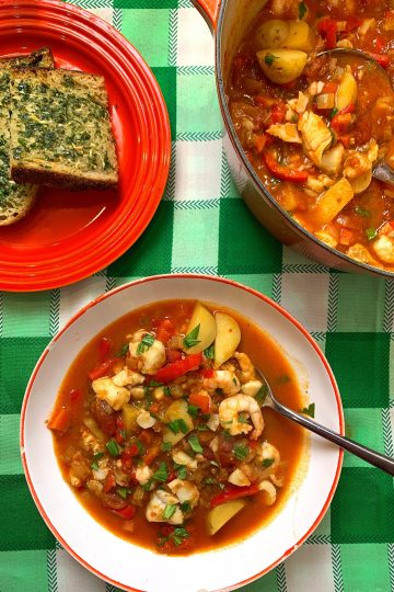 fish stew in a while bowl and a large casserole dish on a green check table cloth with a plate of garlic bread
