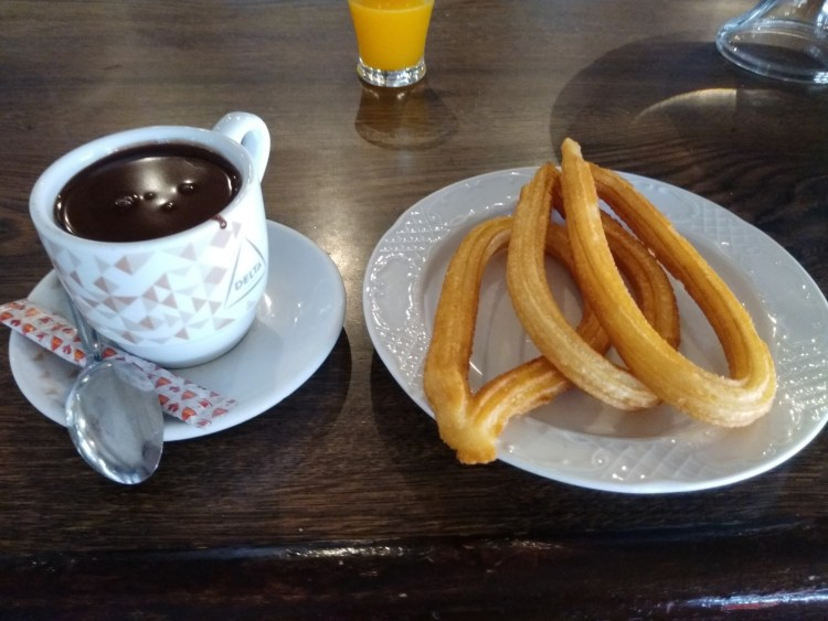 Three churros and a cup of chocolate