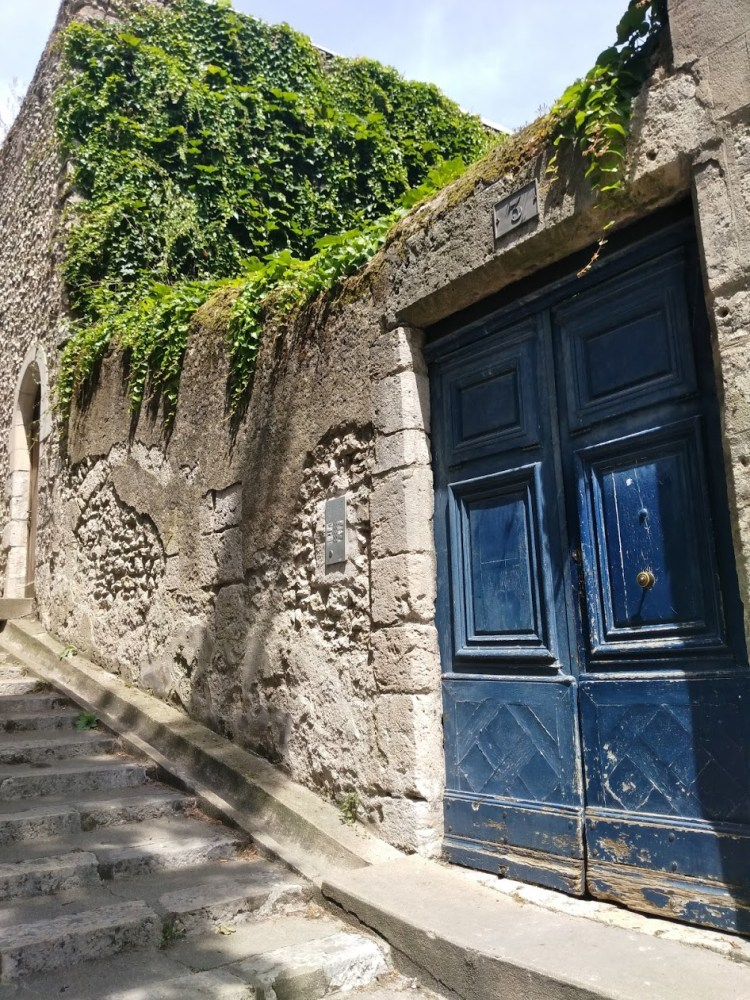 Blue door in stone wall on a pathway
