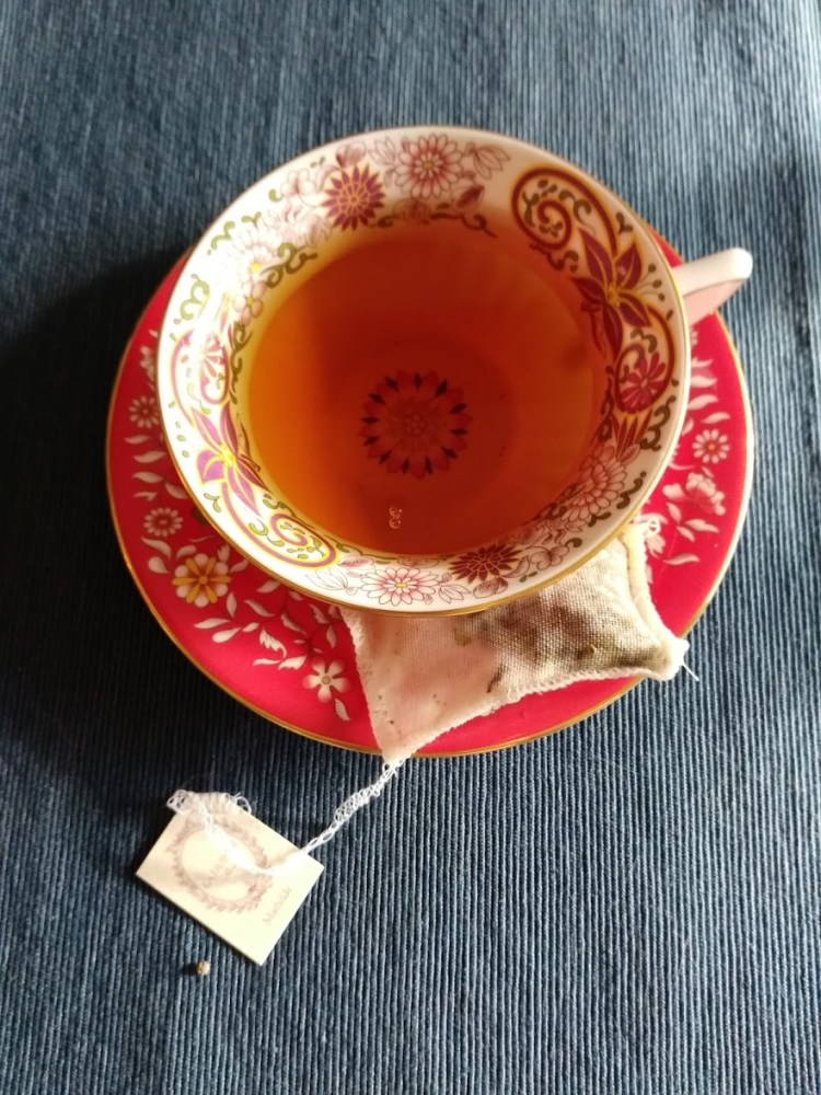 A red saucer with a matching teacup with a teabag on the side reading Ladurée
