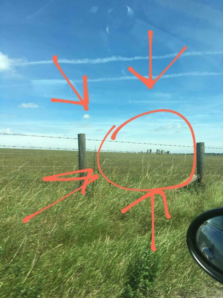 """Real Stonehenge in England. In this photo, Stonehenge appears in the far distance, past a barbed wire fence, in what looks like a farmer's field. This is the """"real"""" Stonehenge in England, but so distant that the photographer kindly circled these ancient monuments with red marker, and added four red arrows for visibility."""