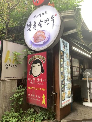 A red sign at the beginning of an alleyway with a drawing of a Korean woman's face. Above is a round sign with Bukchon Sonmandu and a picture of the dumplings. Seoul Travel guide.