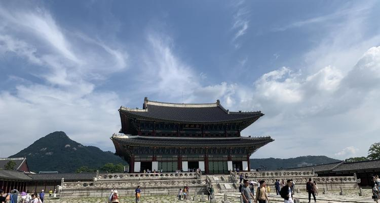 A palace building outlined against a huge blue sky in Seoul travel guide. Mountains are behind the palace, and the courtyard is sparsely populated with tourists. The courtyard is paved with cream colored stones.