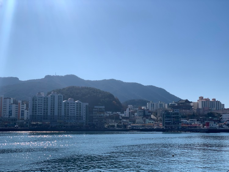 The harbor in Tongyeong travel guide. It's a very sunny day, the water is reflecting and glistening. Layers of hills and mountains are behind city and village scenes across the water.