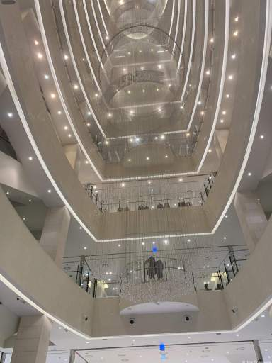 a view up the center of the Shinsaegae Centum City department store. Each floor is white with bright strip lighting and a giant circular chandelier hangs down all 10+ stories.