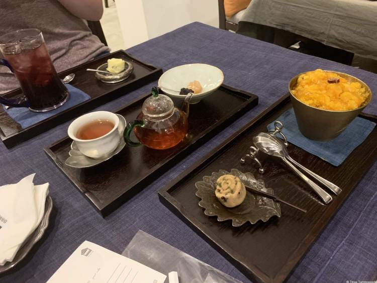 a purple tablecloth with three dark wood trays. Each tray has a traditional snack on a leaf plate. Pumpkin shaved ice, yellow tea, and blackberry iced tea.