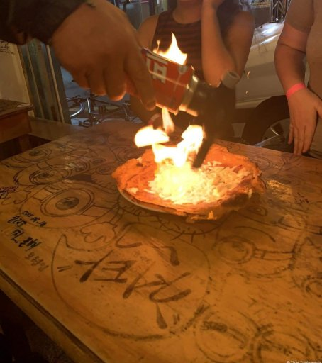 A wood table with many graffiti-like carvings. The pajeon is in the center on a circular plate. An aerosol canister is held above, being lit with a match that creates fire on the plate.