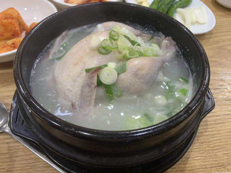 a cloudy white broth with chopped green onions inside. The bowl is a traditional black cast iron bowl. A whole small chicken is inside the bowl.