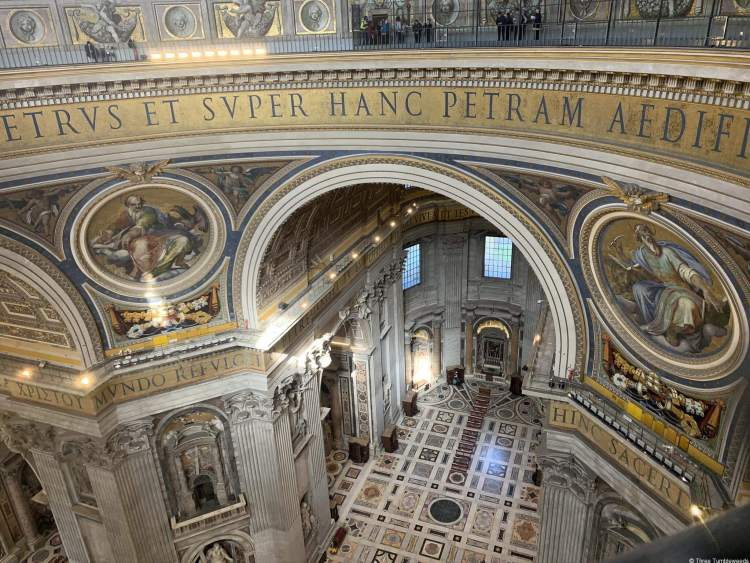 view from above of St. Peter's Basilica letters encircle the round dome on a background of gold, a large archway peaks down at a red and white marble floor, round paintings are on either side of the arch