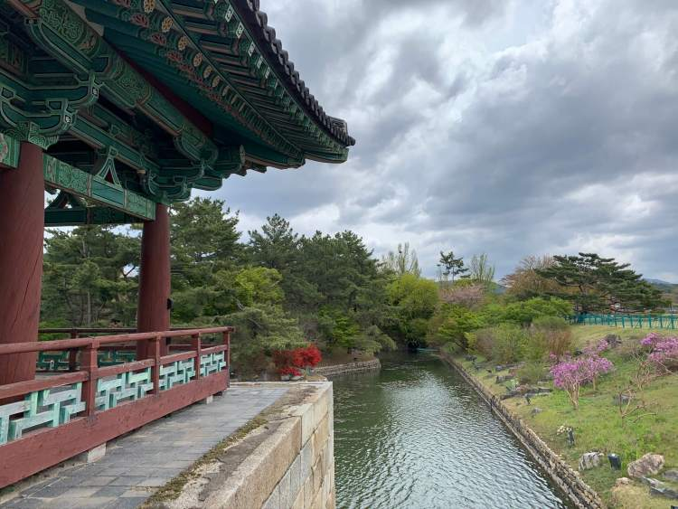 A view of Wolji pond which almost encircles the large red pavillion decorated in green. Spring flowers peak from leafy trees.