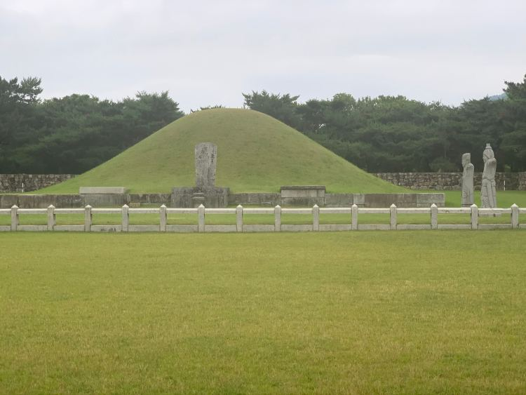 green grass covered mound with a stone fence and traditional Korean stone statues on a cloudy day.