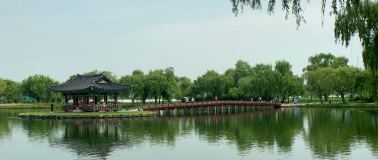 green trees in the background reflecting in a large pond with a red low wooded bridge reaching into the middle. A traditional pavilion is built on the small island in the middle of the pond, connected to the bridge. June 2020 travel