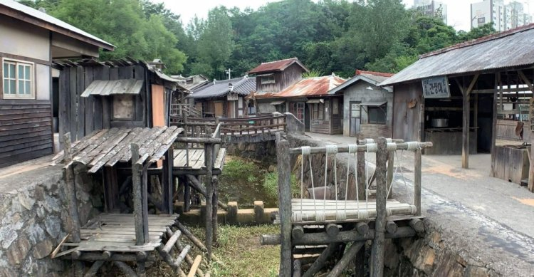A shanty town, a small man-made river area runs between wooden houses, ramshackle bridged cross the divide.