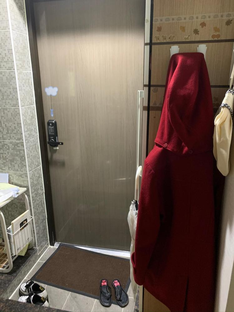 entryway of a korean apartment tour. A brown door with an electronic lock, a brown mat and two pairs of shoes. To the right are some command hooks holding a red coat