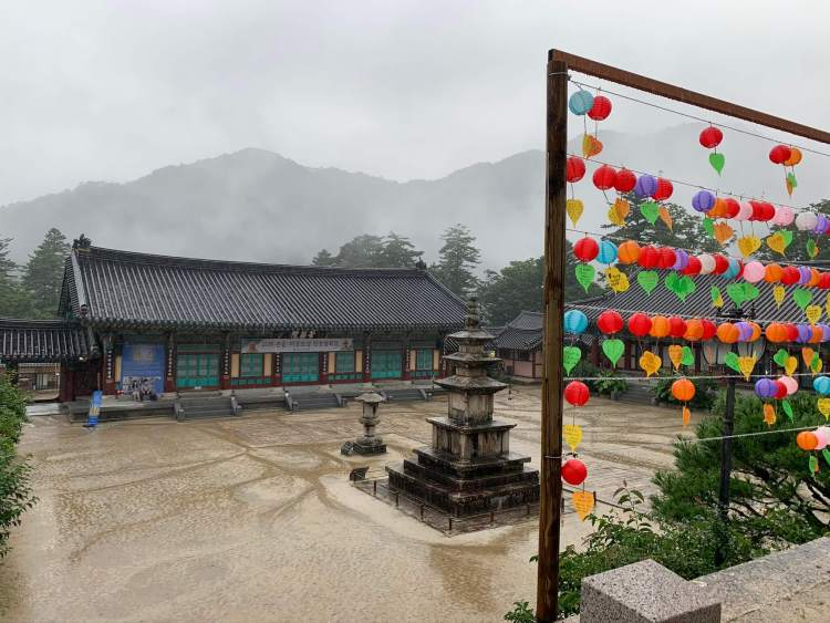 A view of a temple building in the rain with misty gray mountains outlined in the back. In the foreground is a stone monument and a wooden structure from which many multicolored lanterns hang.