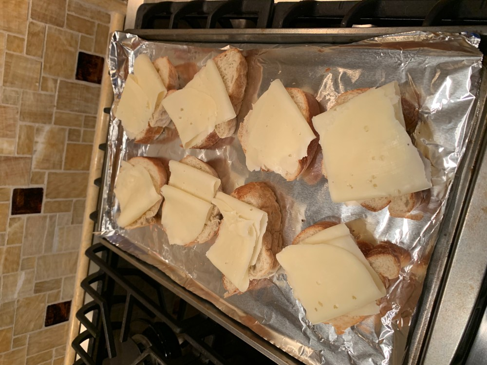 french bread slices with slices of swiss cheese folded on top sitting on top of a sheet pan covered with foil. Waiting to go into the oven on top of the stove.