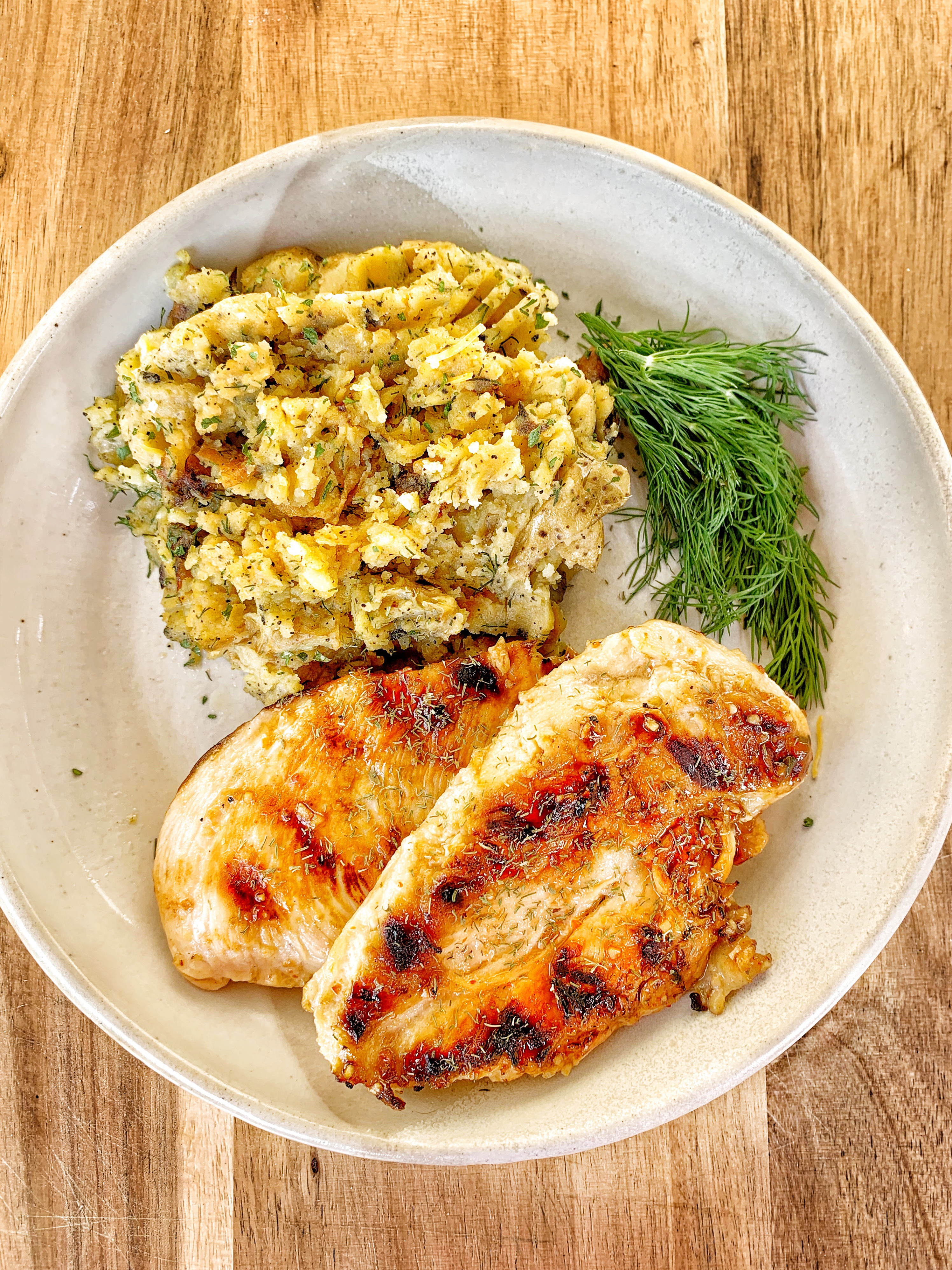 two grilled chicken breasts, mashed potatoes and a sprig of dill