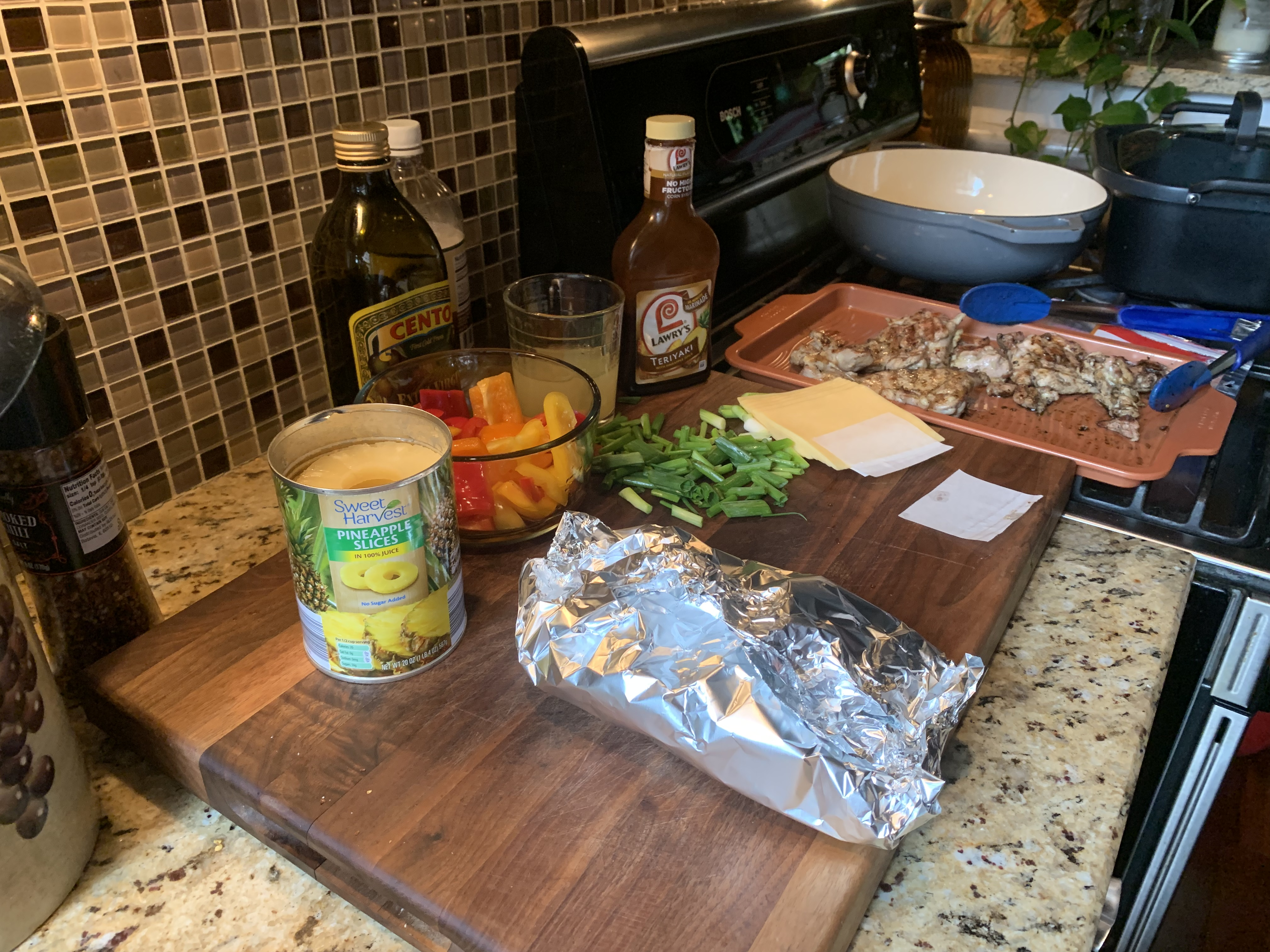 a food prep station is pictured with peppers, pineapple, chicken, cheese and foil