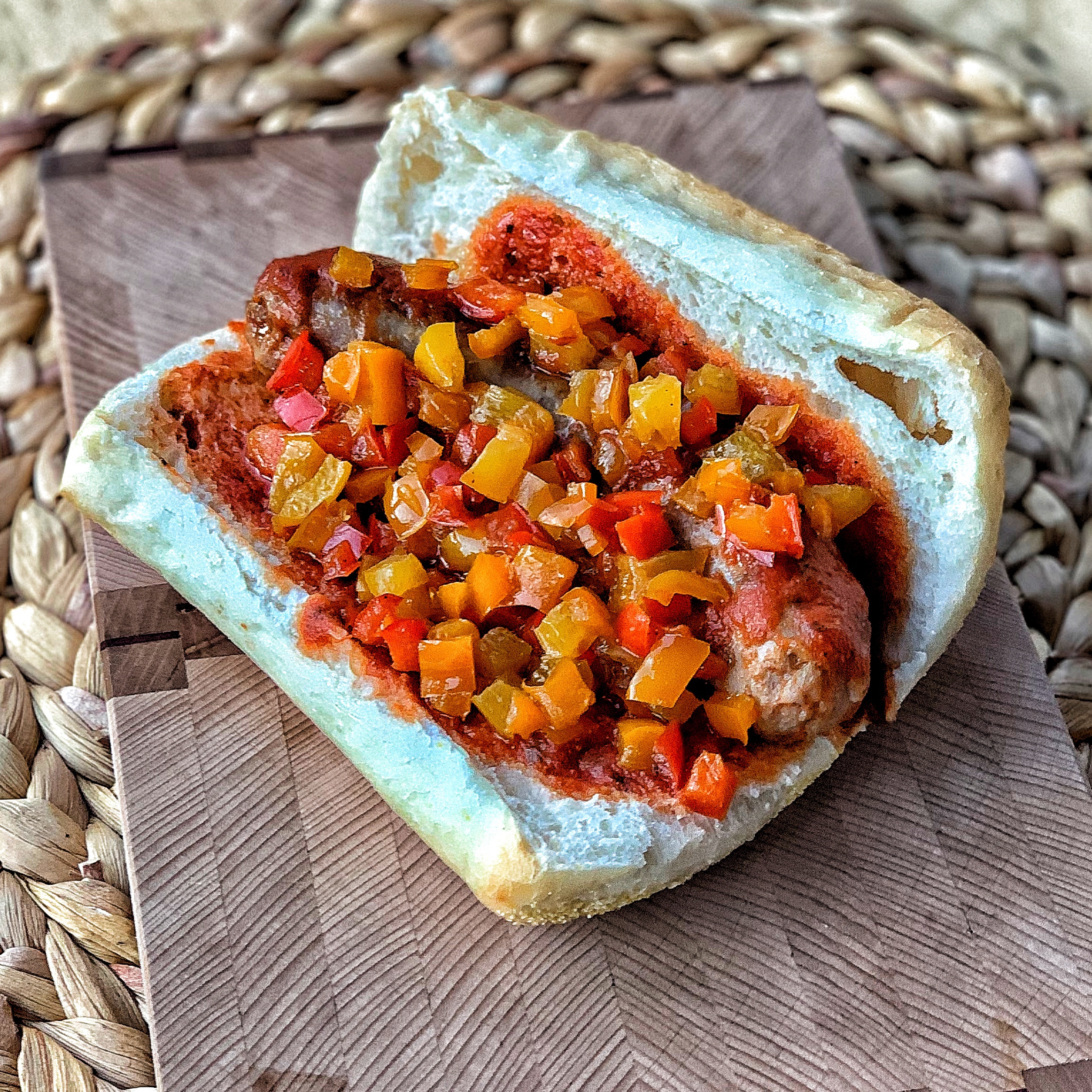 Open faced sausage sadnwich with colorful peppers and marinara sauce.