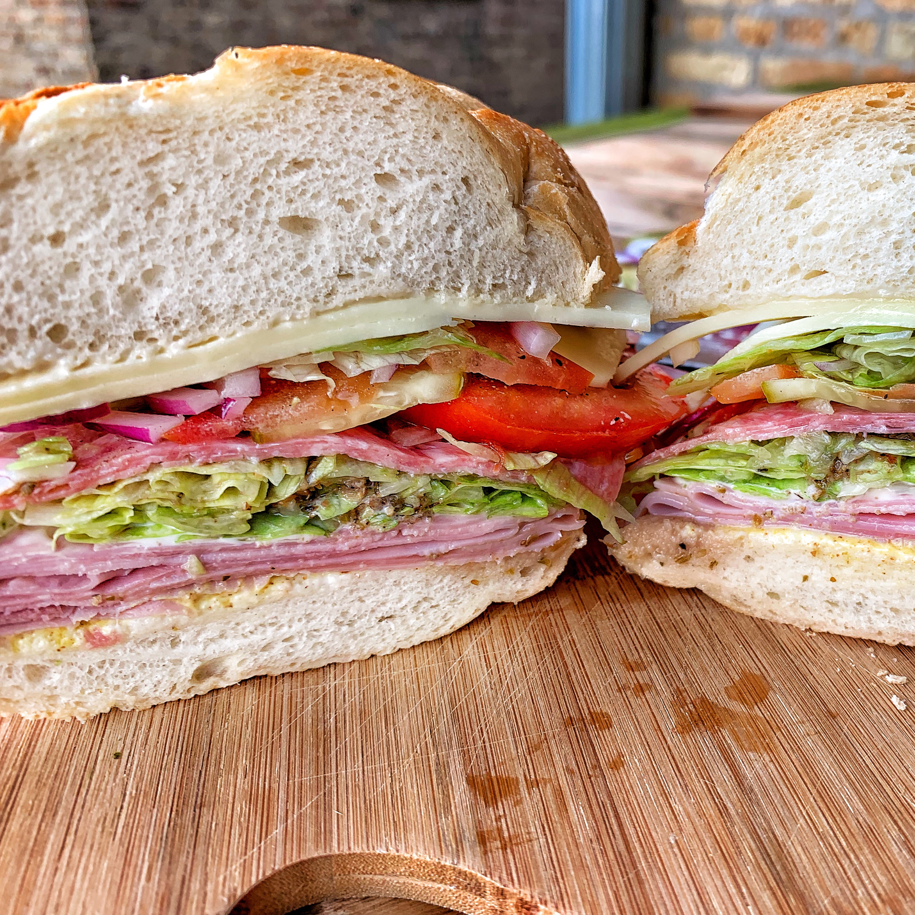 Picture of a sandwich cut in half showing all the layers of deli meat, cheese and veggies.
