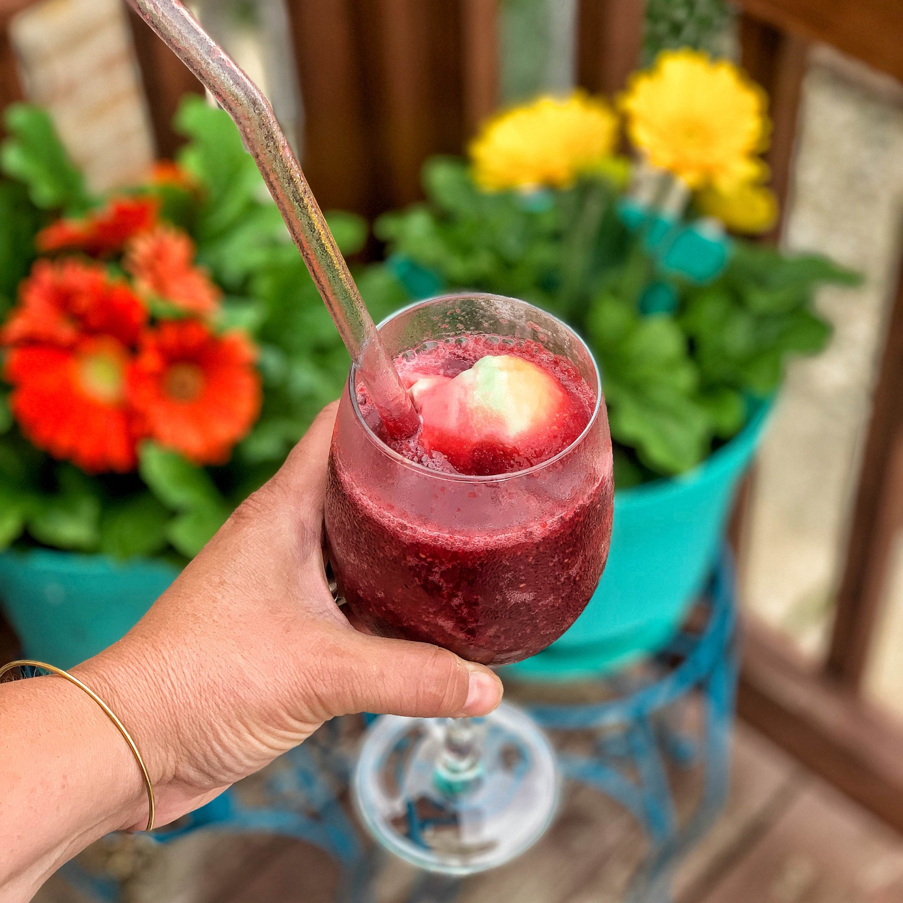 A wine glass with a fruity red frozen red wine