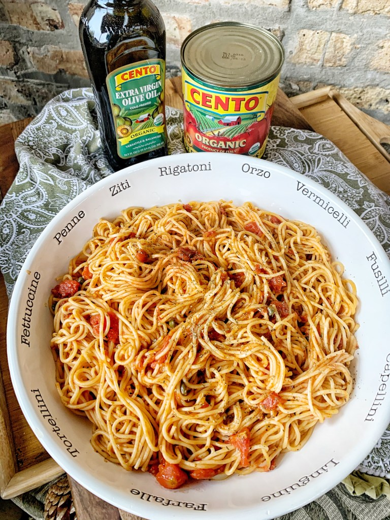 Tomato pasta with thin spaghetti in a white bowl goes great with the lemon caper chicken cutlets