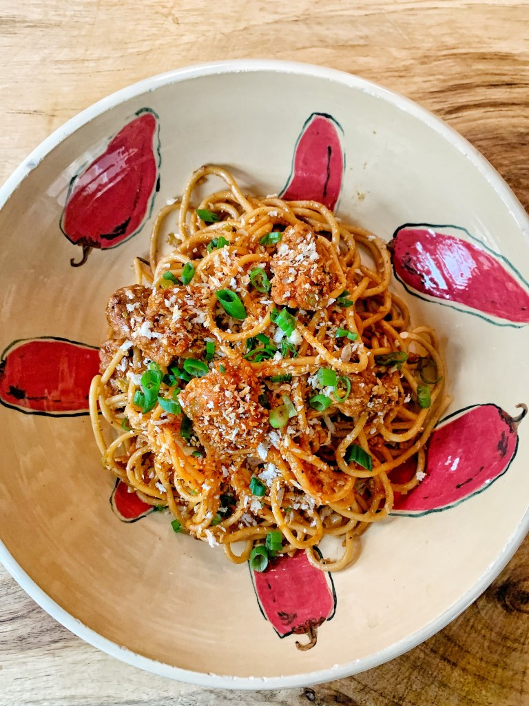 A bowl of king pao spaghetti with crispy chicken and toasted sesame panko.