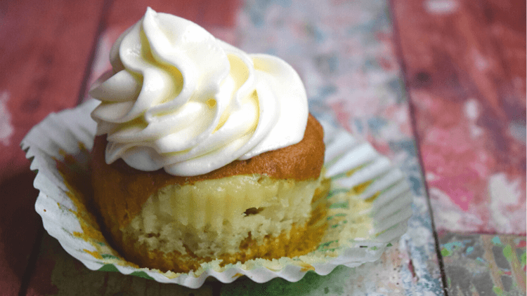 A close up of a single pumpkin cheesecake cupcake with the cupcake liner pulled down to reveal the cheesecake.