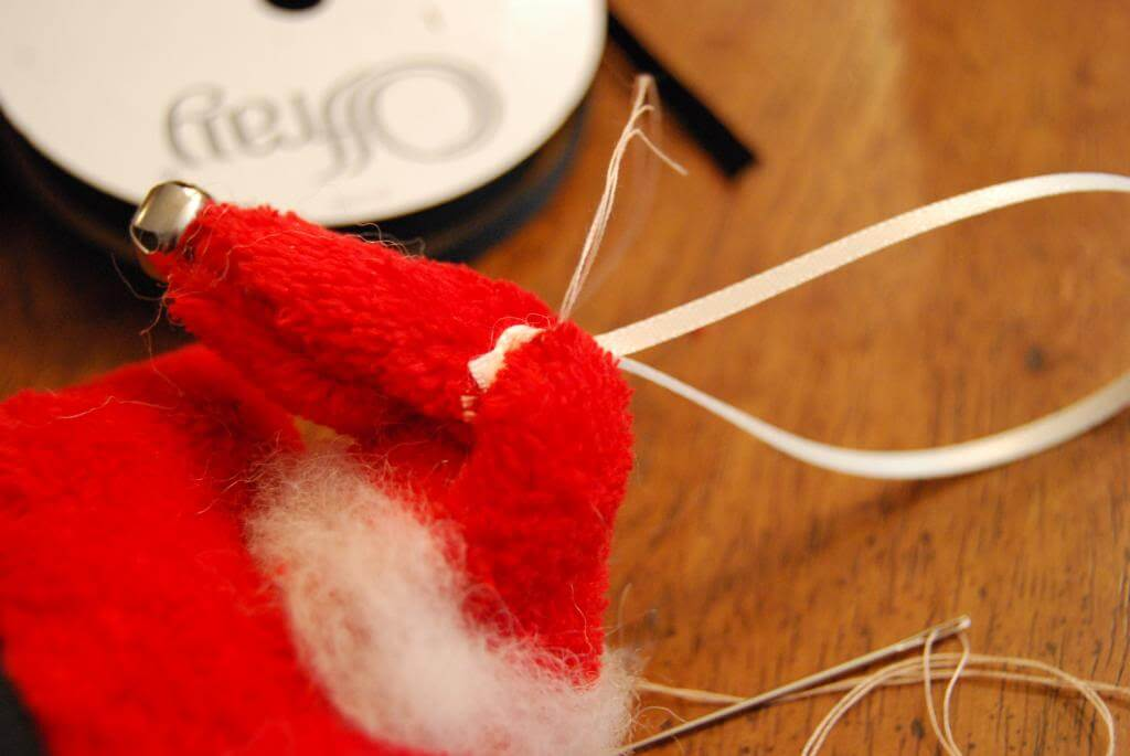 Sew a ribbon to the back of Santa's hat to hang him on the tree.