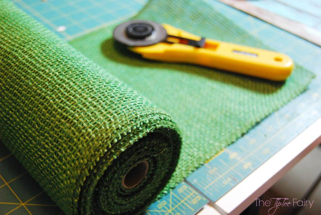 A roll of green burlap ribbon on the cutting mat with a rotary cutter.
