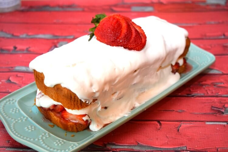 The finished view of the No Bake Strawberry Shortcake with a giant strawberry sliced on top and whipped cream running down the sides.