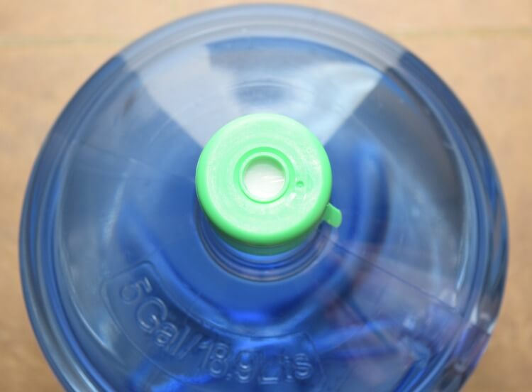 The top of the water bottle with the insert that prevents it from spilling out when loading.