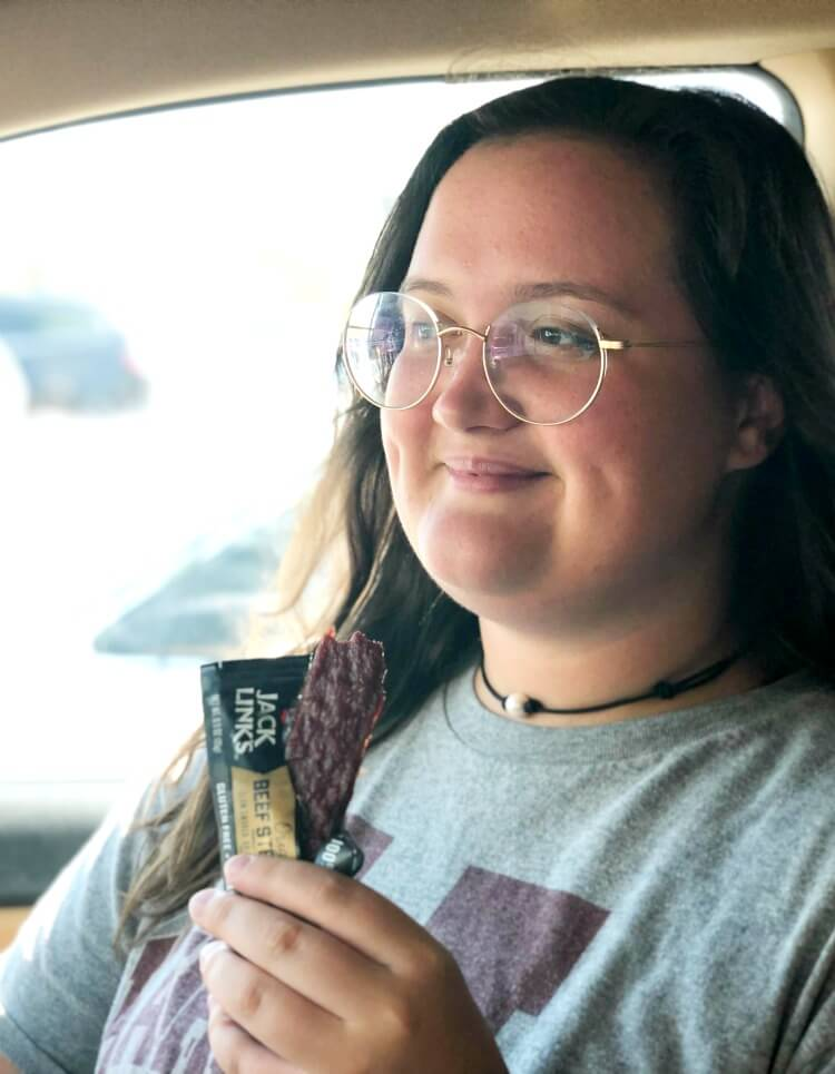 Teen girl eating a Jack Link's Bar in the car.