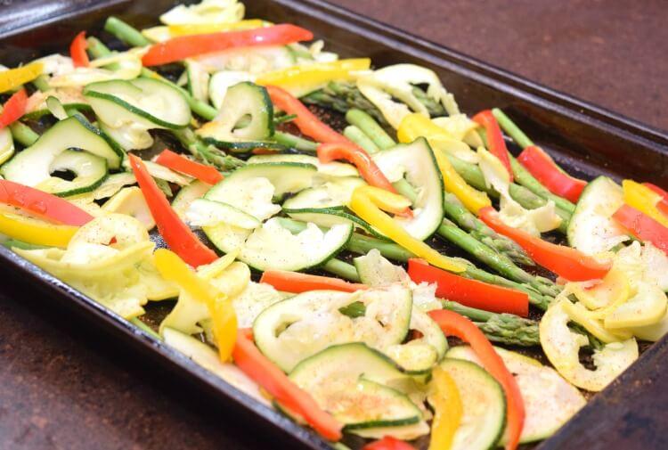 Seasoning the sheet pan veggies.