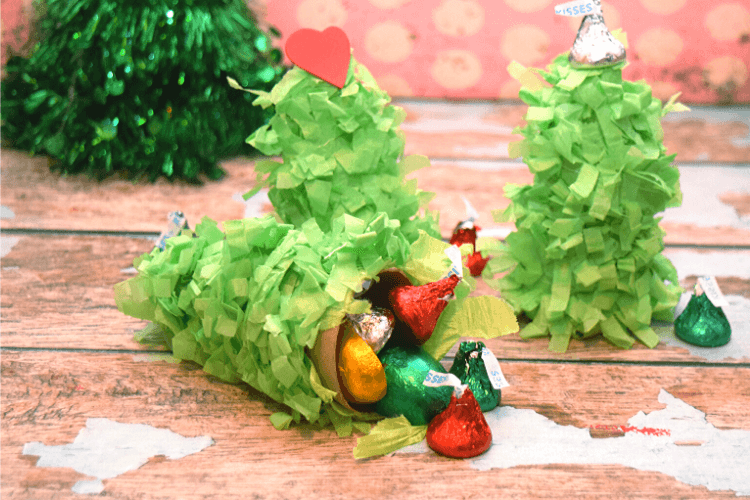 The mini christmas pinata opened on its side and spilling candy.